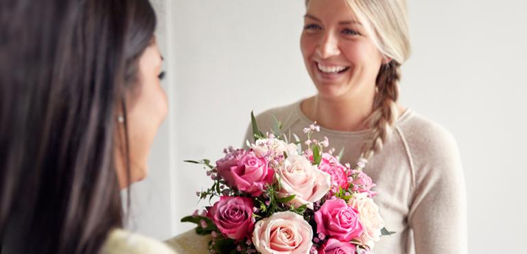 Zwei Freundinnen die einen rosa Rosen Blumenstrauß verschenken
